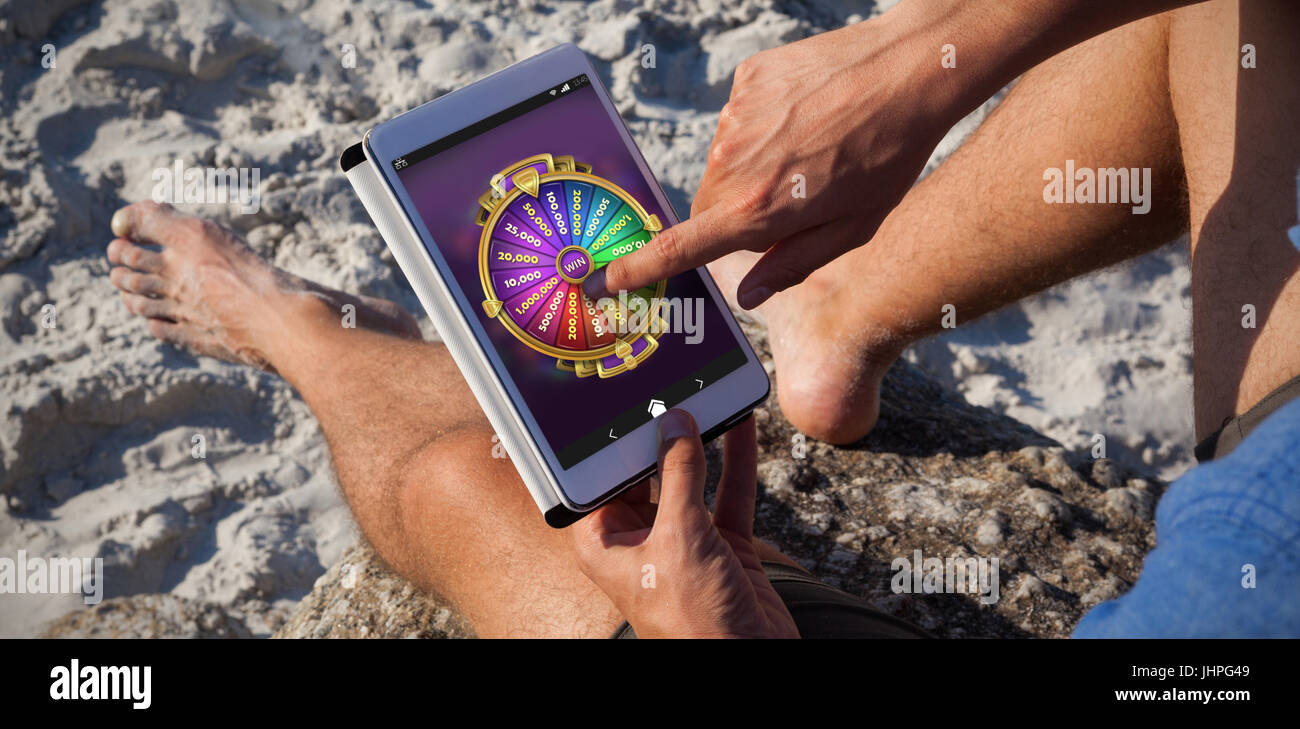 Multi colored fortune of wheel on mobile display against man using digital tablet on the beach - Stock Image