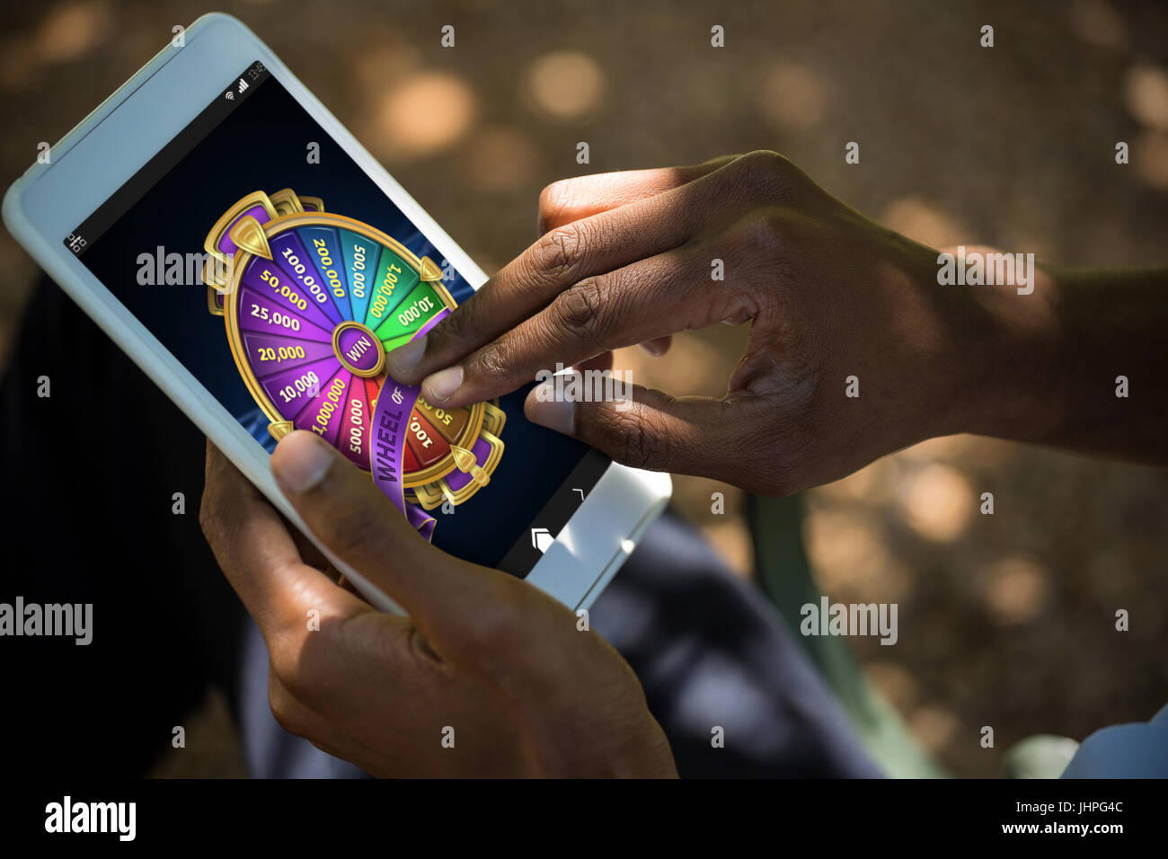 Colorful wheel of fortune on mobile display against man using tablet computer Stock Photo