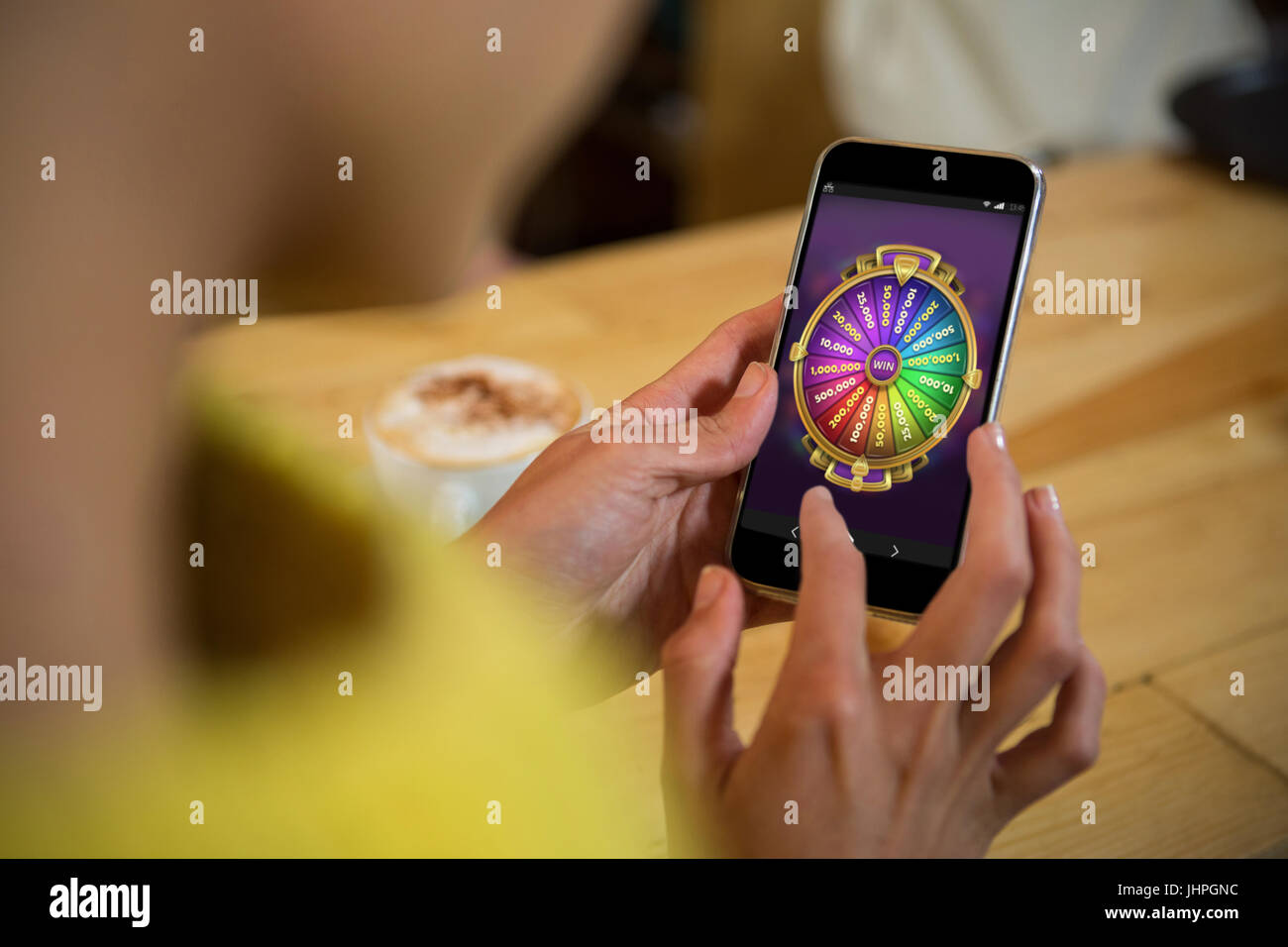 Multi colored fortune of wheel on mobile display against woman using mobile phone at table in cafe - Stock Image