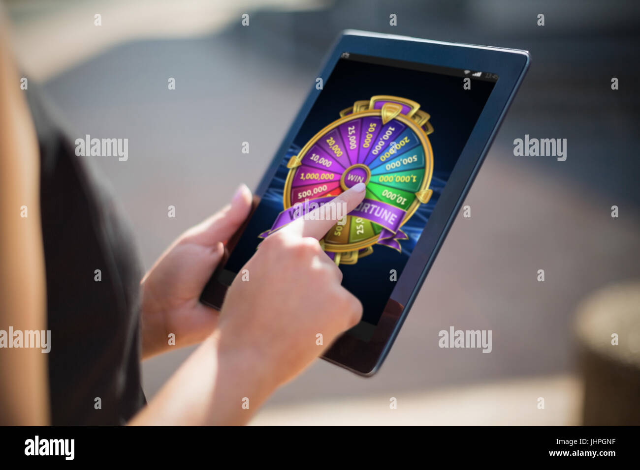 Colorful wheel of fortune on mobile display against businesswoman using digital tablet - Stock Image