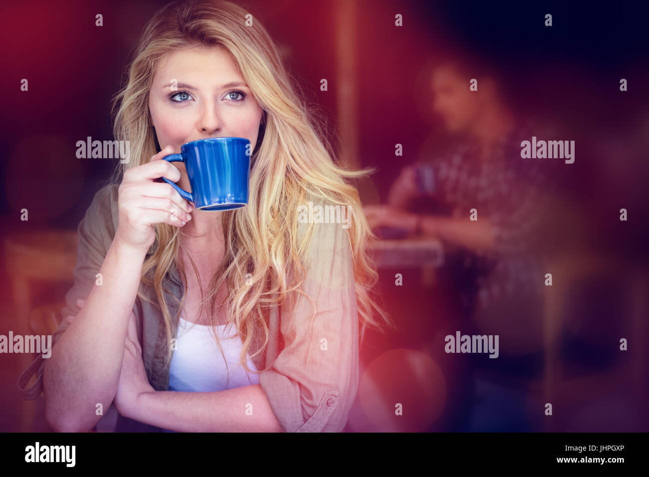 Young woman drinking coffee with man sitting in background at cafe - Stock Image