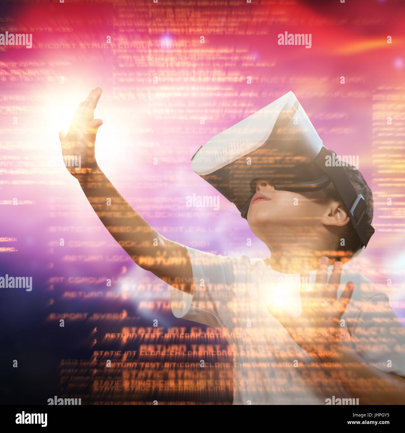 Boy using virtual reality simulator glasses against vector image of illuminated orange light - Stock Image