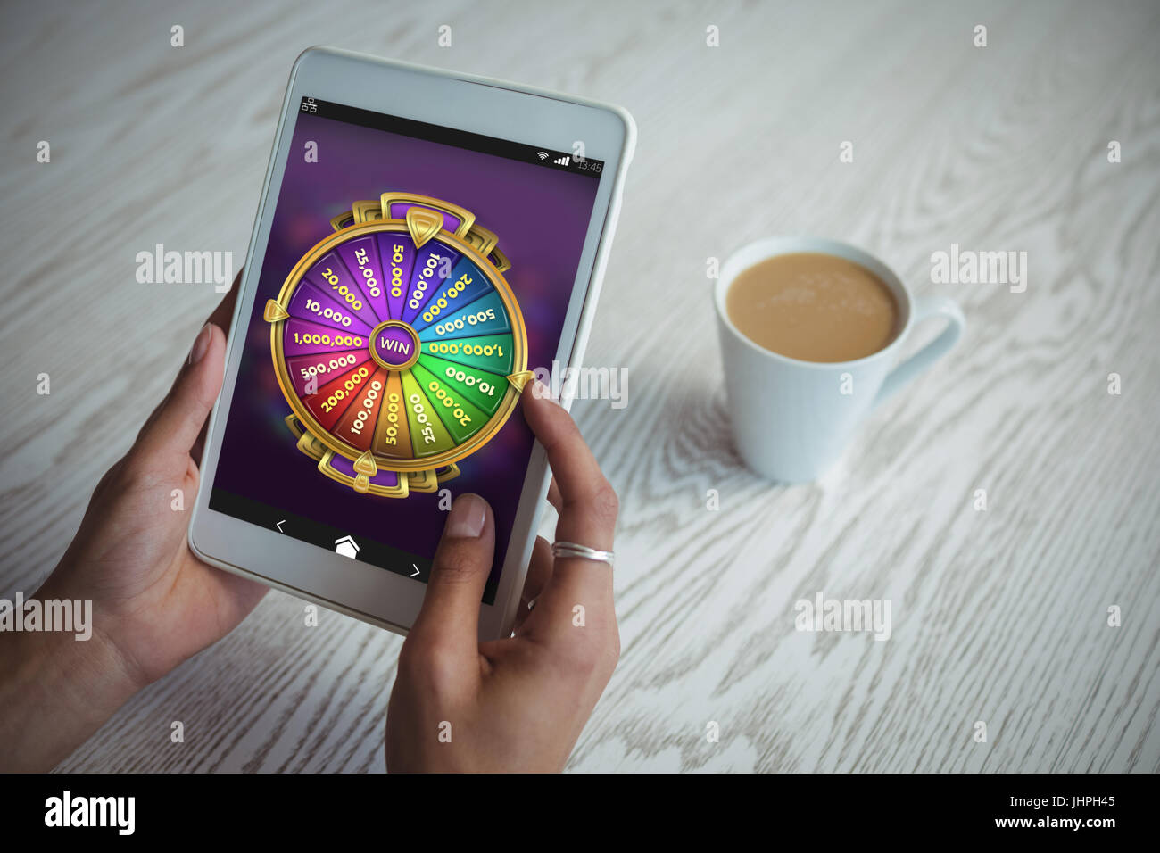 Multi colored fortune of wheel on mobile display against cropped hands of woman holding tablet at table - Stock Image