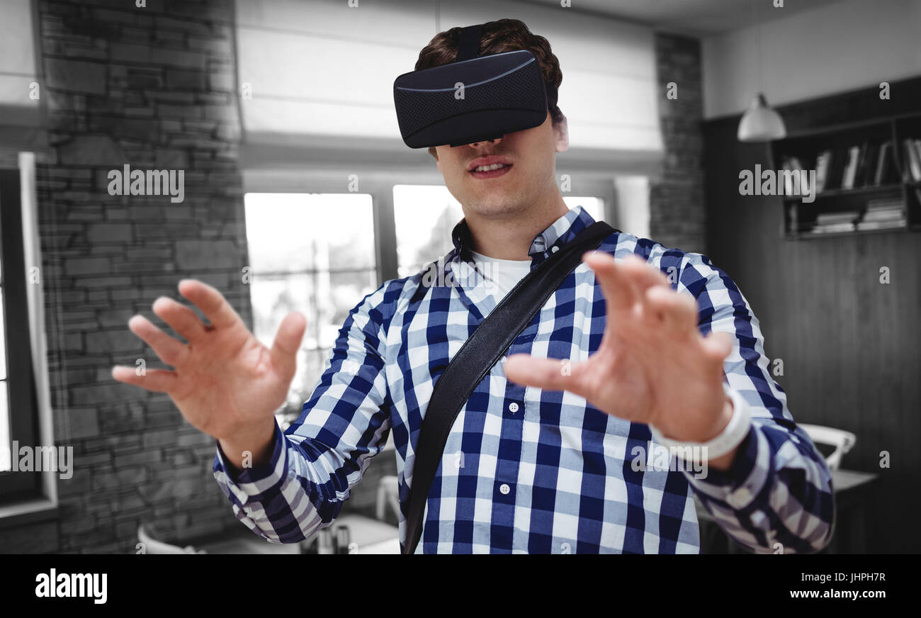 Young man using virtual reality simulator glasses against empty chairs and tables - Stock Image