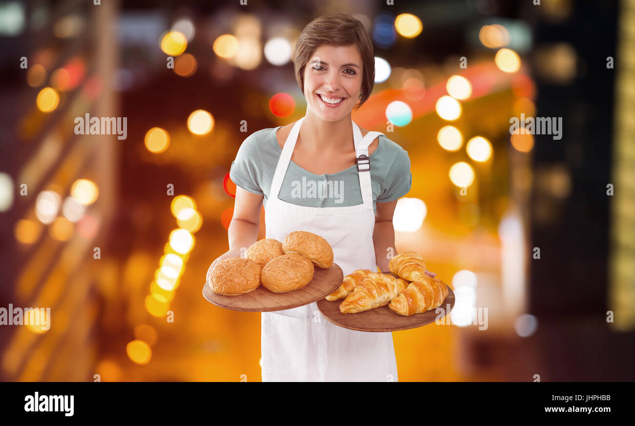 Waitress holding croissant on a tray  against glowing road in city at night - Stock Image