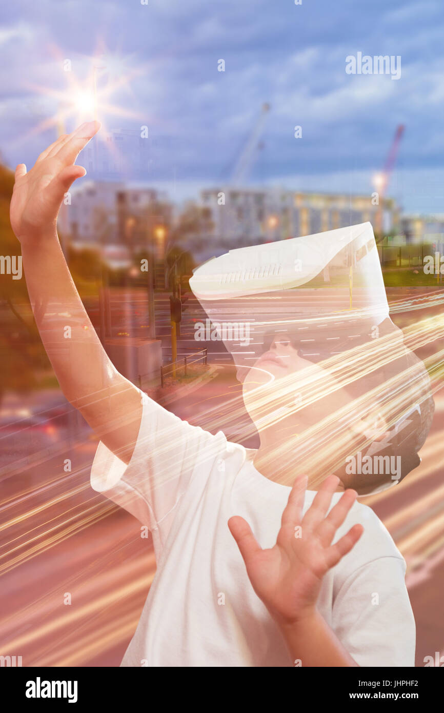 Boy using virtual reality simulator glasses against light trails on city street - Stock Image
