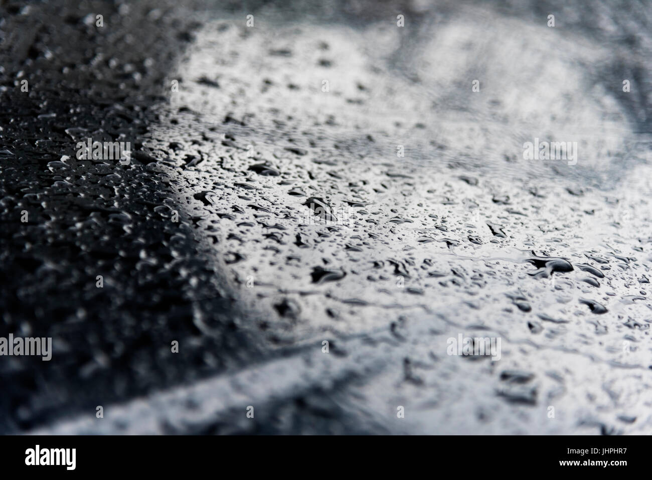 Drops of water at dark polished metal surface, background - Stock Image