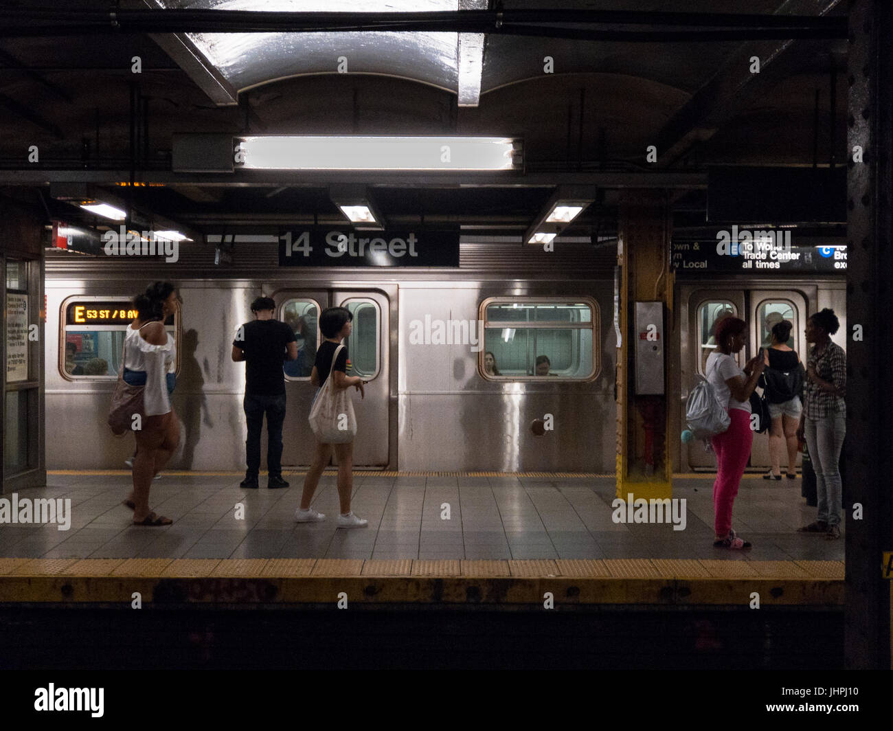 New York, NY -- July 12, 2017 -- People waiting for the train at the New York City subway station at 8th Avenue - Stock Image