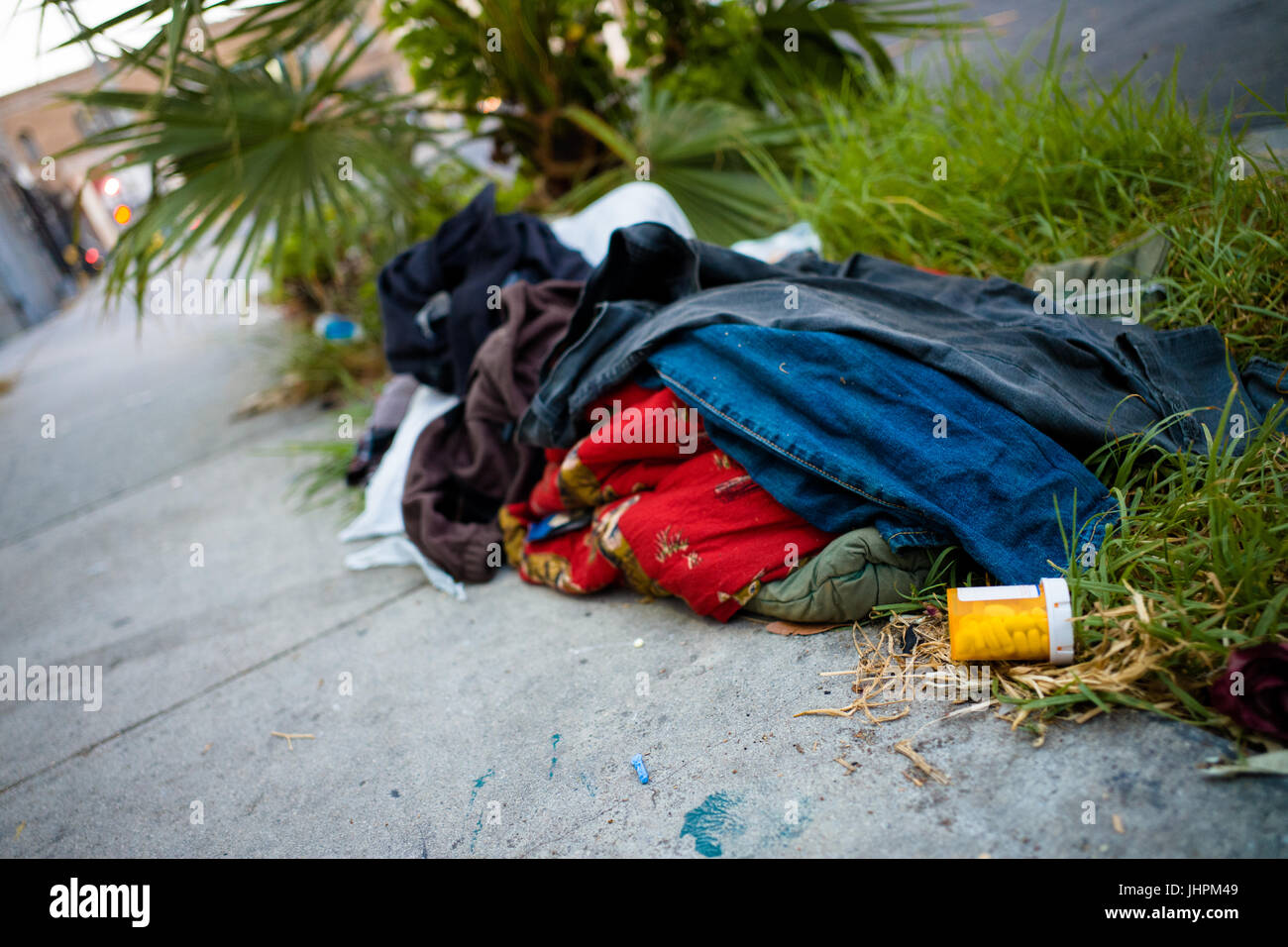 Pharmaceutical pills and scattered clothes lay abandoned on a city sidewalk in Hollywood, Los Angeles, California. - Stock Image