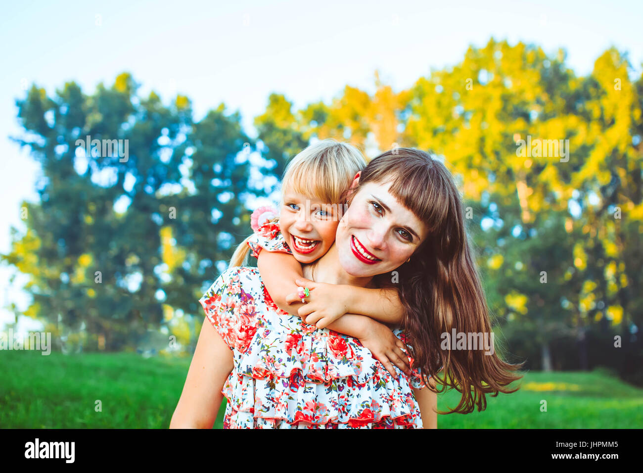 Cute young daughter on a piggy back ride with her mother. Looking at camera. - Stock Image