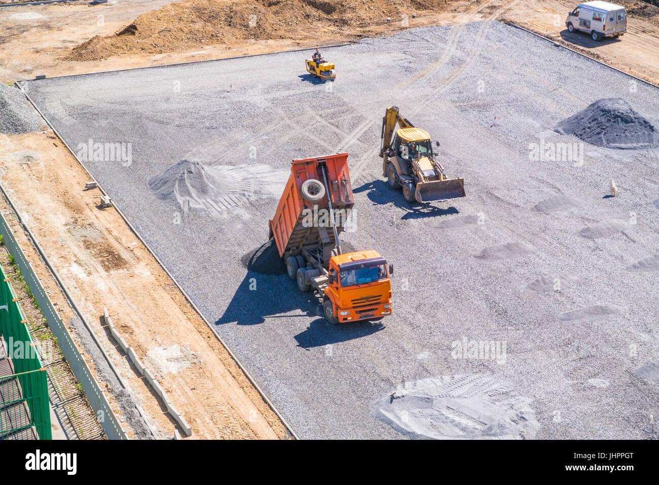 Dump truck unloads asphalt at the construction site of the school stadium. - Stock Image
