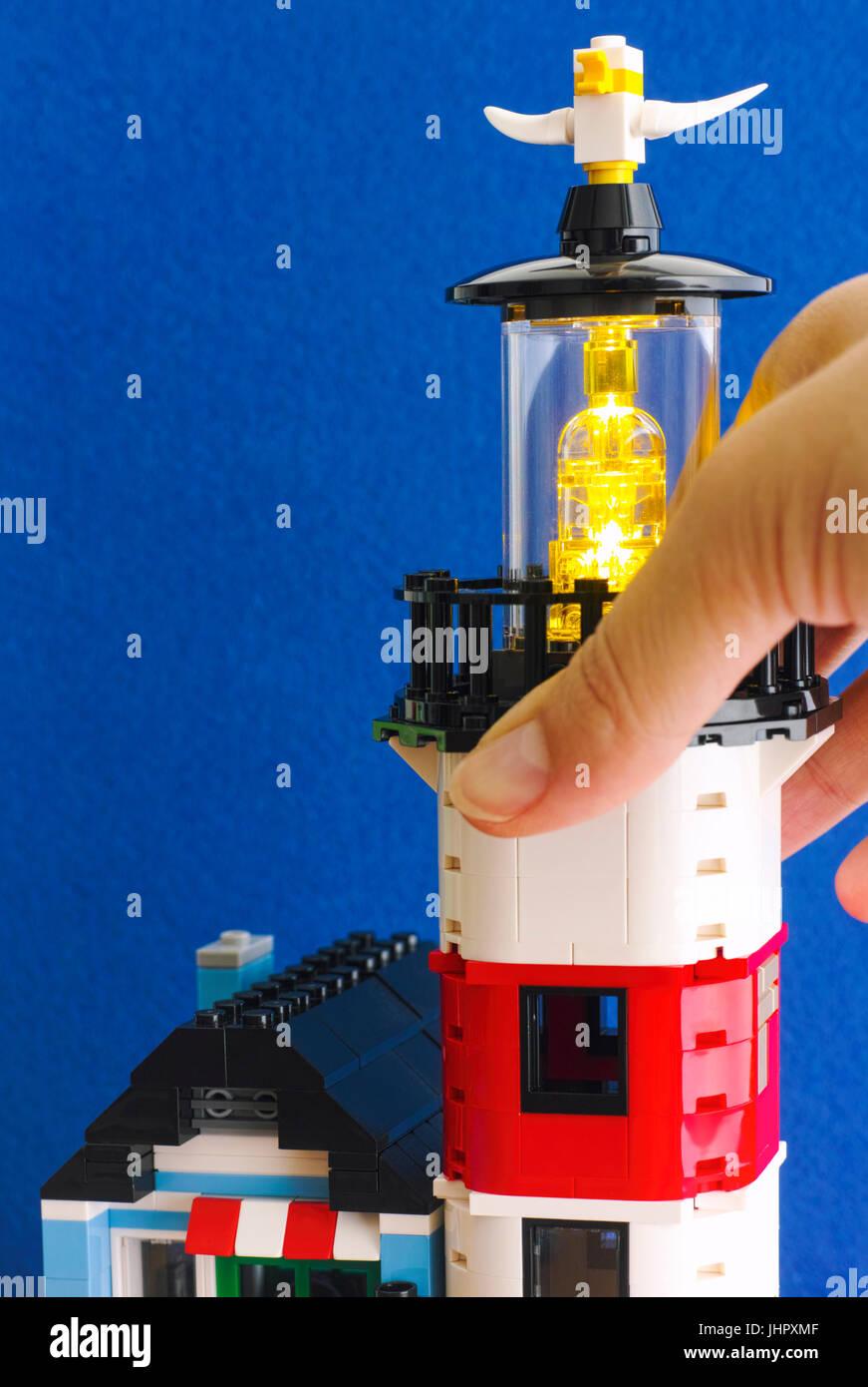 Tambov, Russian Federation - June 15, 2017 Woman hand turns on Lego Lighthouse light. Blue background. Studio shot. - Stock Image