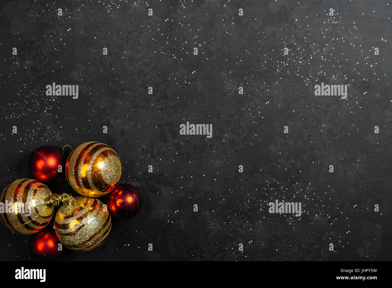 Christmas baubles on black background with glitters Stock Photo