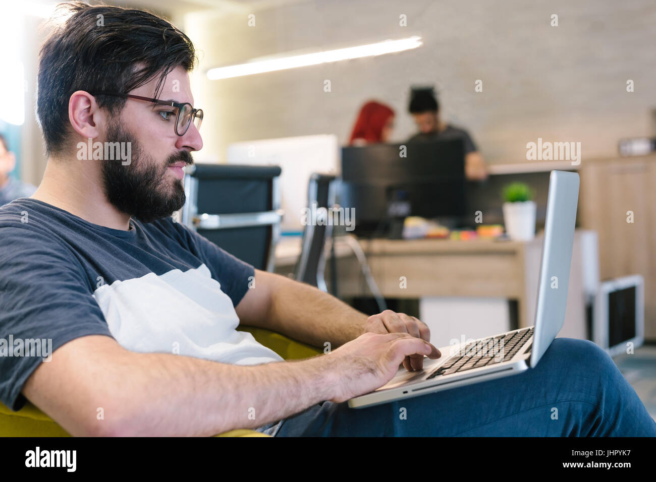 Photo bearded banker working in a modern office overtime. Man sitting in yellow chair at night. Using contemporary - Stock Image