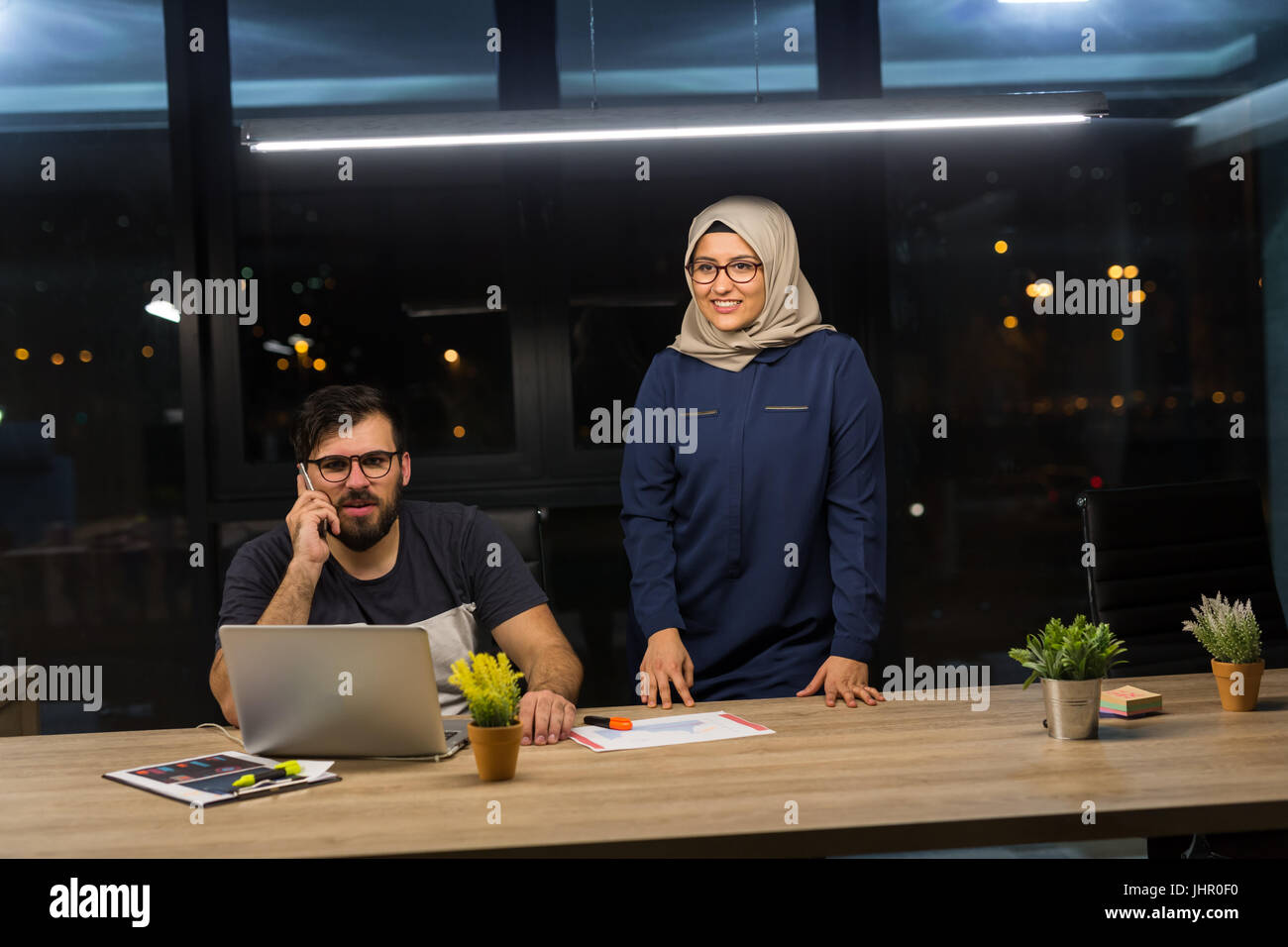 Man collaborating with woman wearing hijab. Working overtime in modern office. - Stock Image