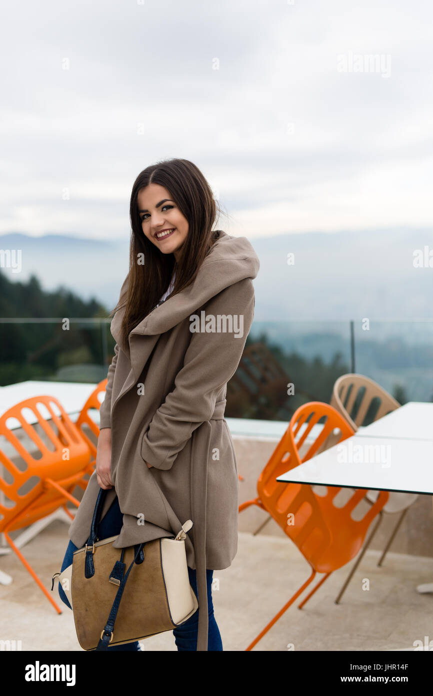 awesome vintage woman looking away in trench coat at fall time - Stock Image