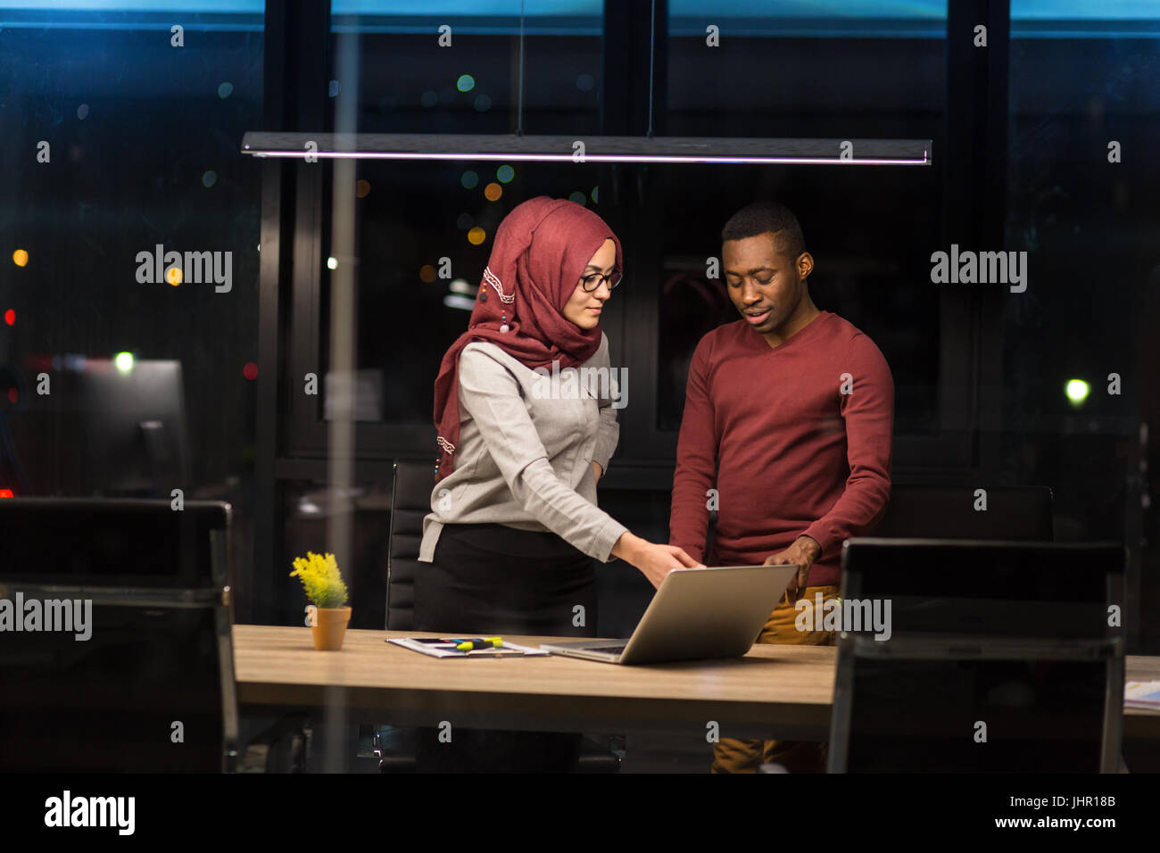 Arab woman and African man collaborating in the office working overtime. - Stock Image