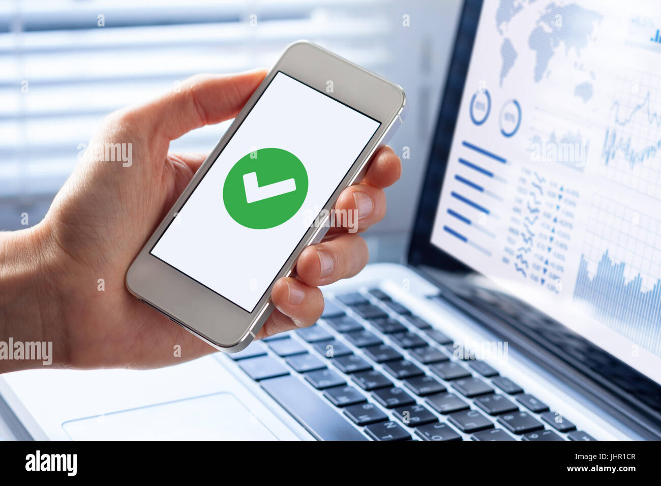 Hand holding a smartphone with a green checkmark icon on the screen to show a validated, confirmed, completed or Stock Photo