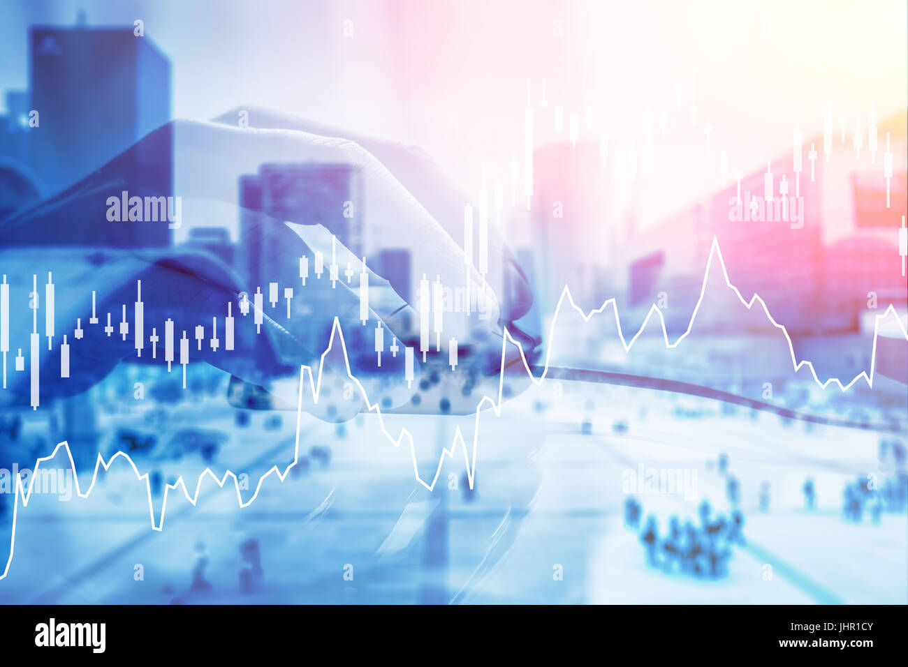 Hand holding computer mouse with digital stock exchange investment financial charts in foreground and business district - Stock Image