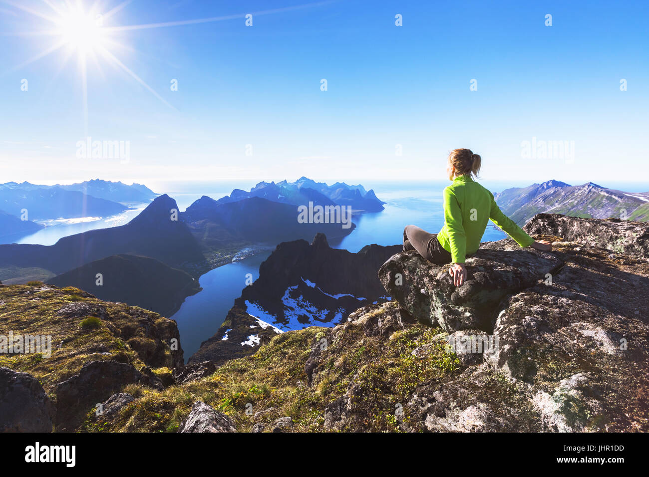 Woman hiker relaxing at the top of the mountain and looking at incredible views of a  Norwegian fjord on Senja Island, - Stock Image