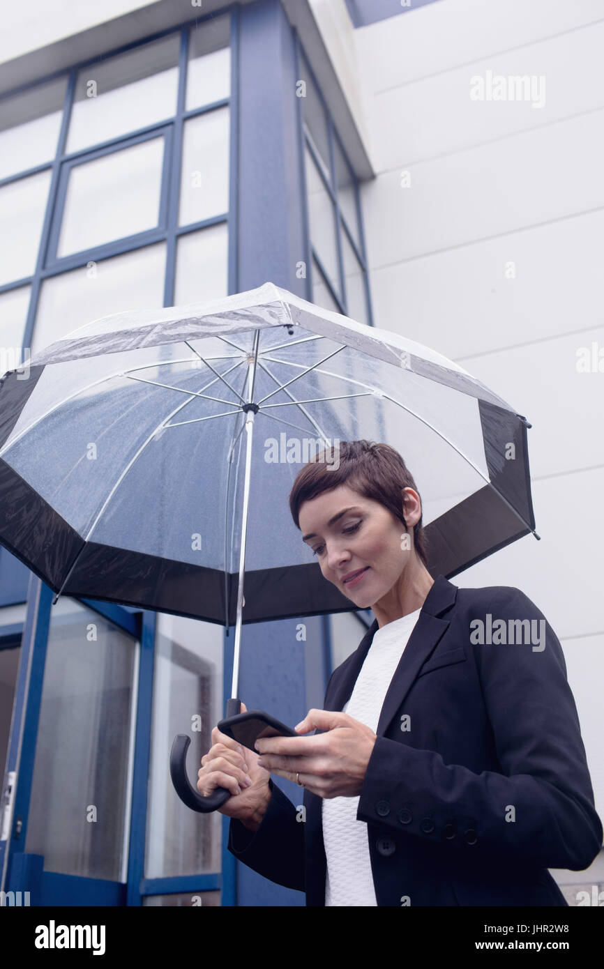 Businesswoman using mobile phone while holding umbrella in office premises - Stock Image