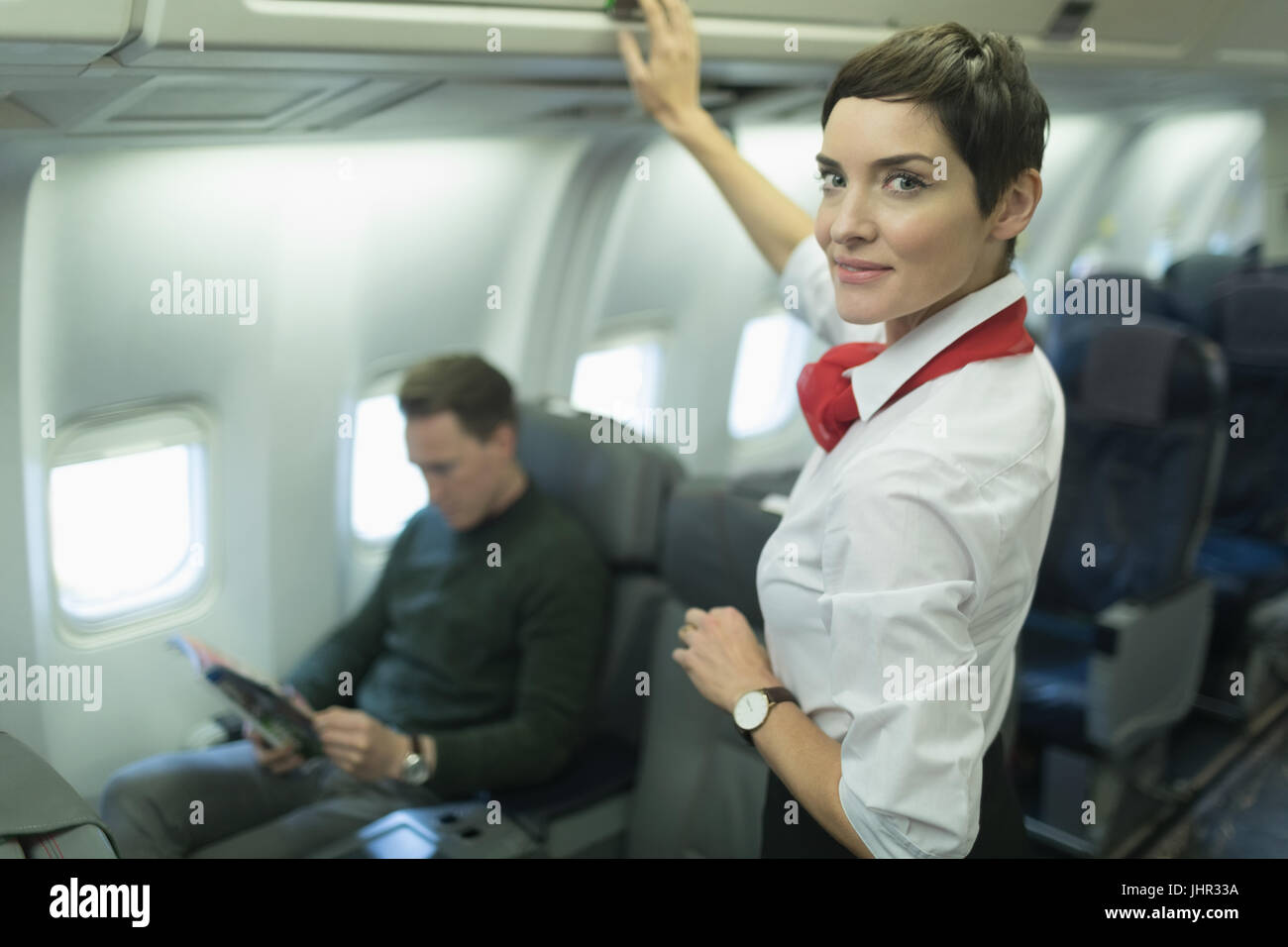 Confident air hostess smiling at camera while passenger reading magazine in an aircraft - Stock Image