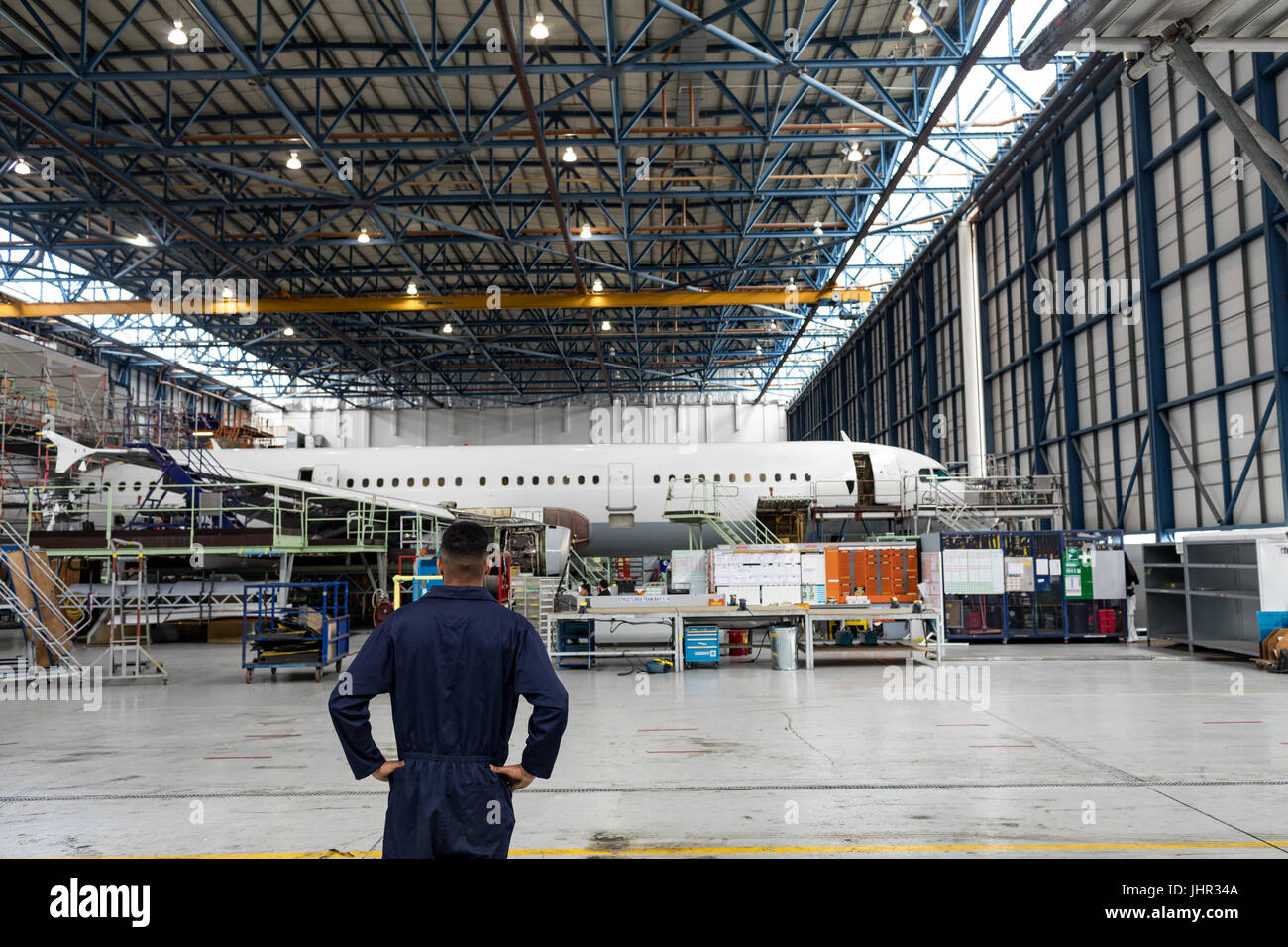Rear view of aircraft maintenance engineer standing at airlines maintenance facility - Stock Image