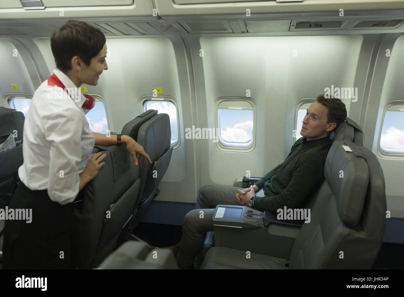Air hostess interacting with passenger while travelling in an aircraft - Stock Image