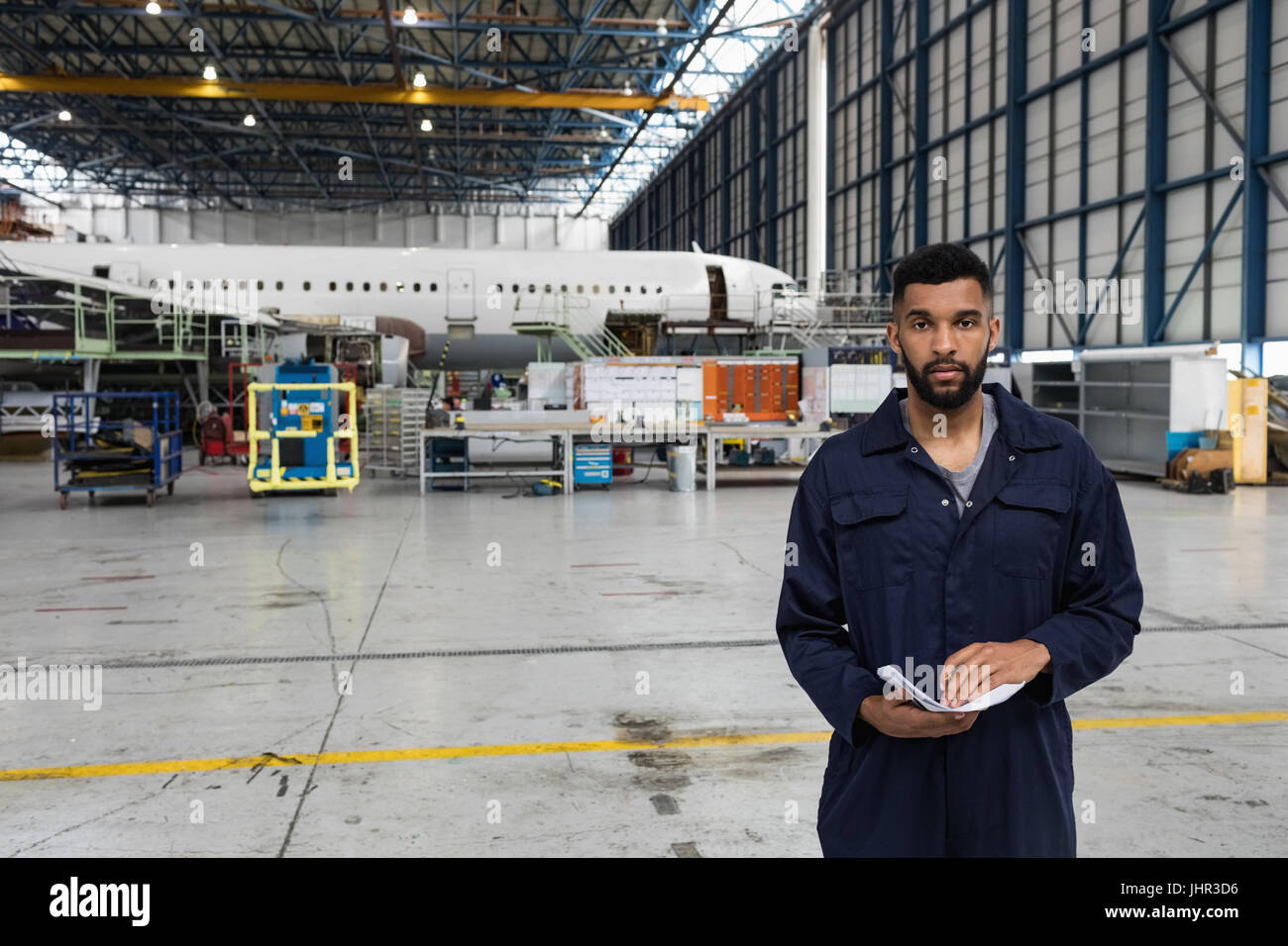 Portrait of aircraft maintenance engineer standing at airlines maintenance facility - Stock Image