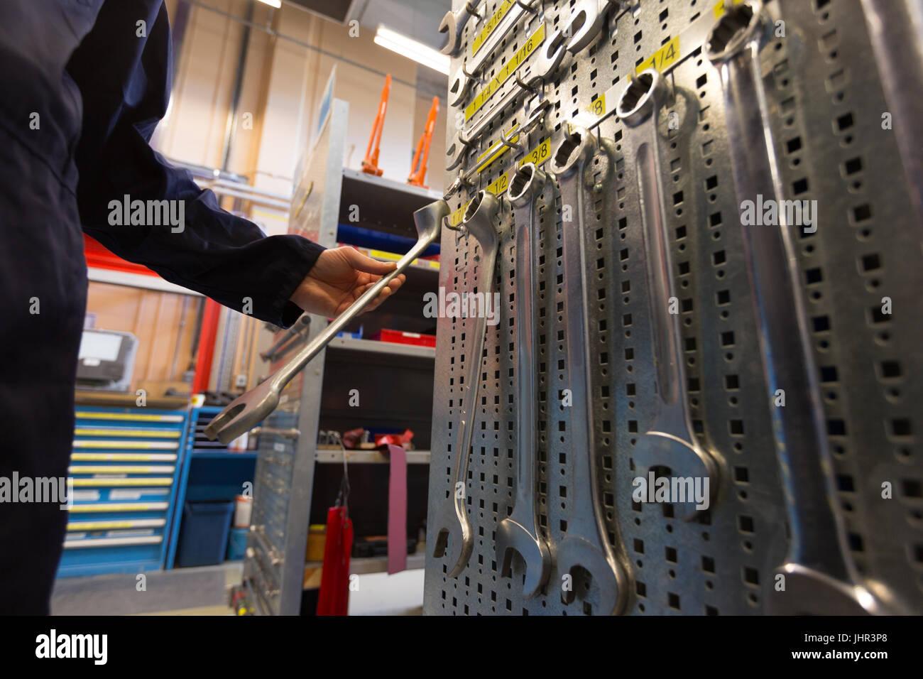 Male aircraft maintenance engineer examining various work tool at airlines maintenance facility - Stock Image