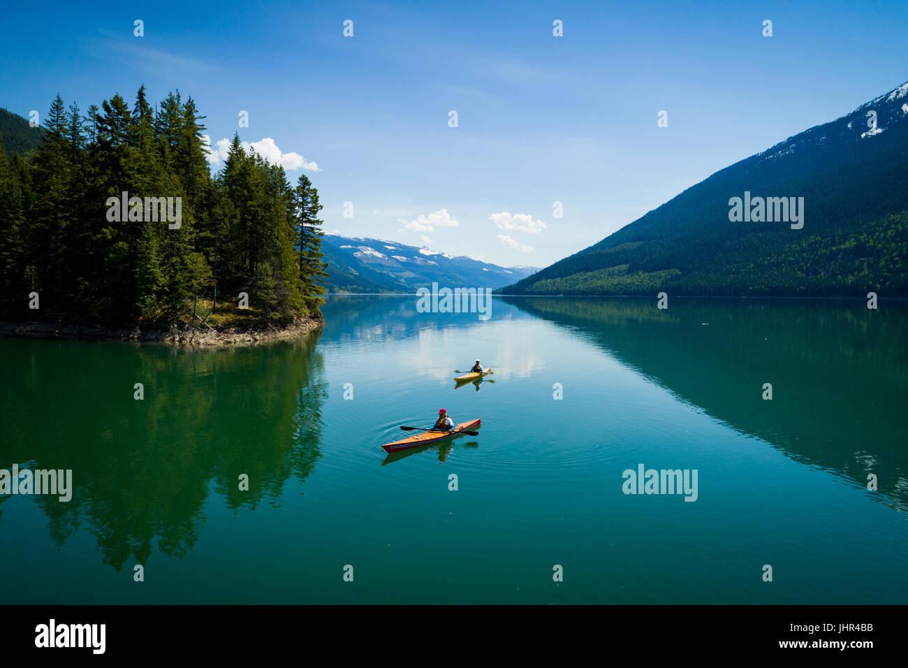 Couple enjoying water sport against  blue sky - Stock Image