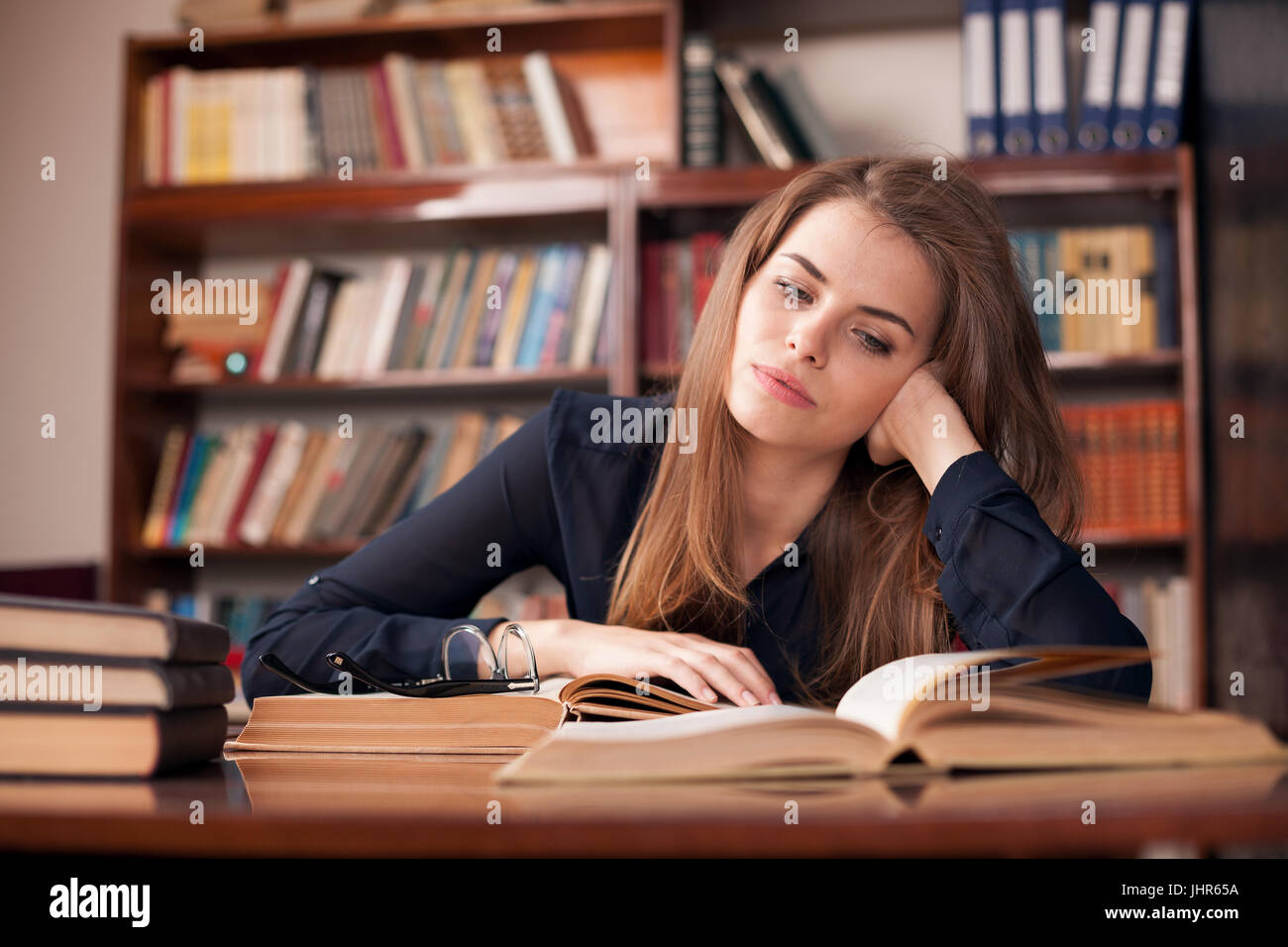 girl student sits in the library reading and preparing for the exam Stock Photo