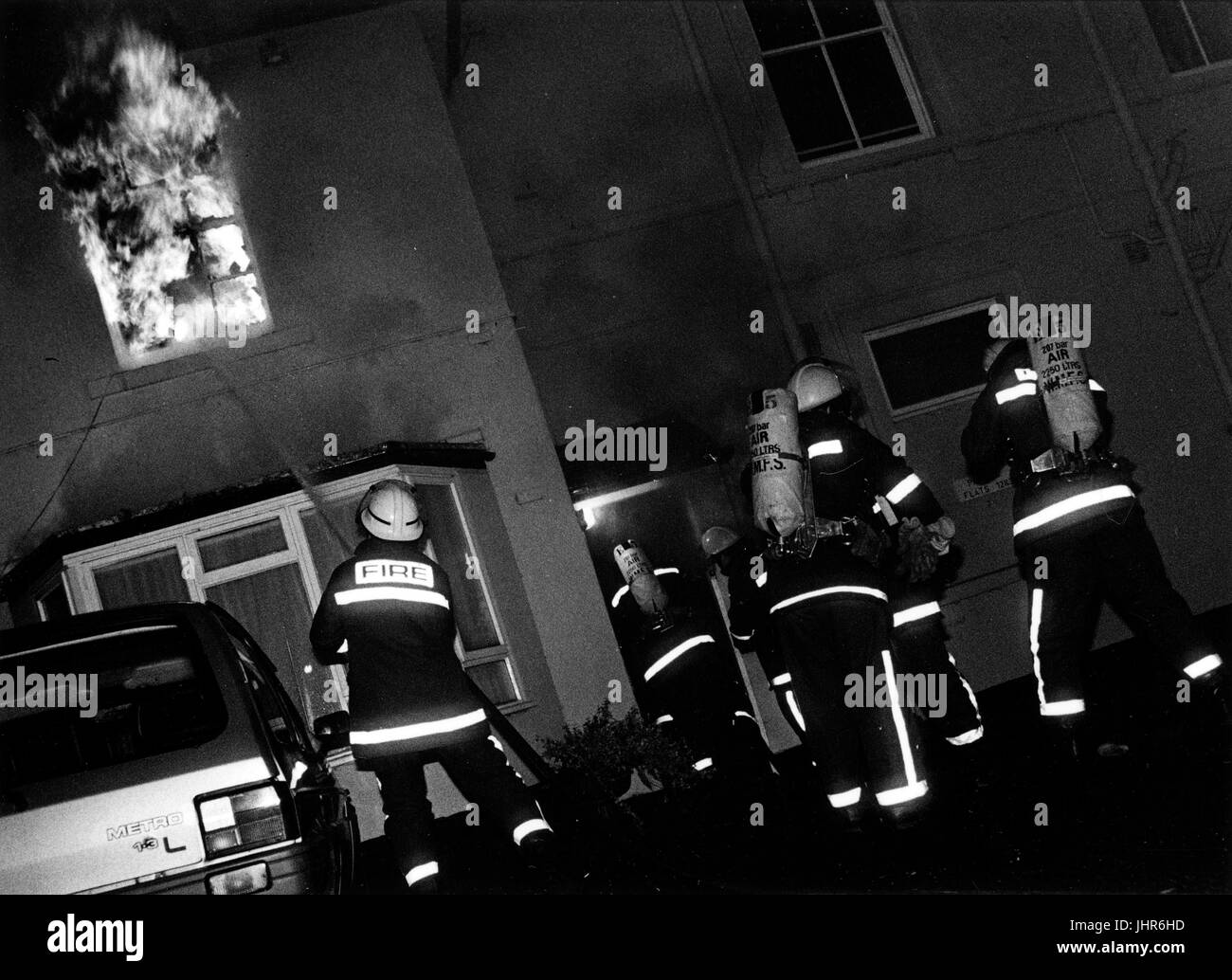 Fire Fighters of West Midlands Fire Brigade enter burning building in search of a 'persons reported' - Stock Image