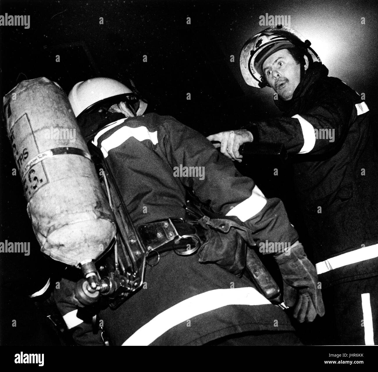 Station officer from West Midlands Fire Brigade gives orders to fire fighter about to enter burning building in - Stock Image