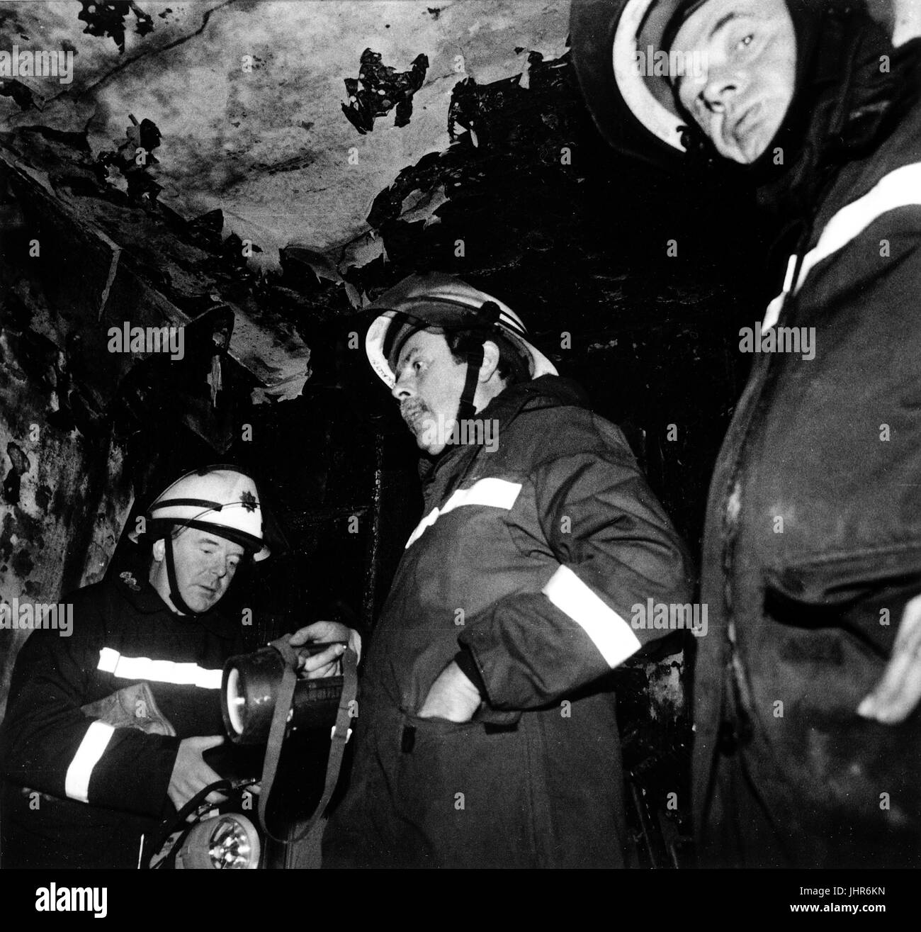 Station officer from West Midlands Fire Brigade (centre) inspects aftermath of flat fire in Wolverhampton - Stock Image