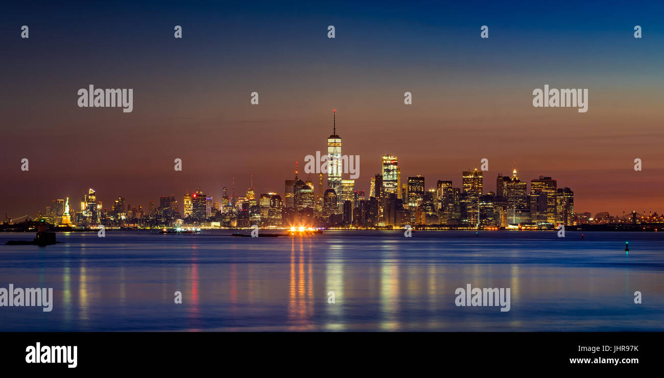 First light of the day on Lower Manhattan skyscrapers from New York City Harbor. Financial District and Midtown - Stock Image