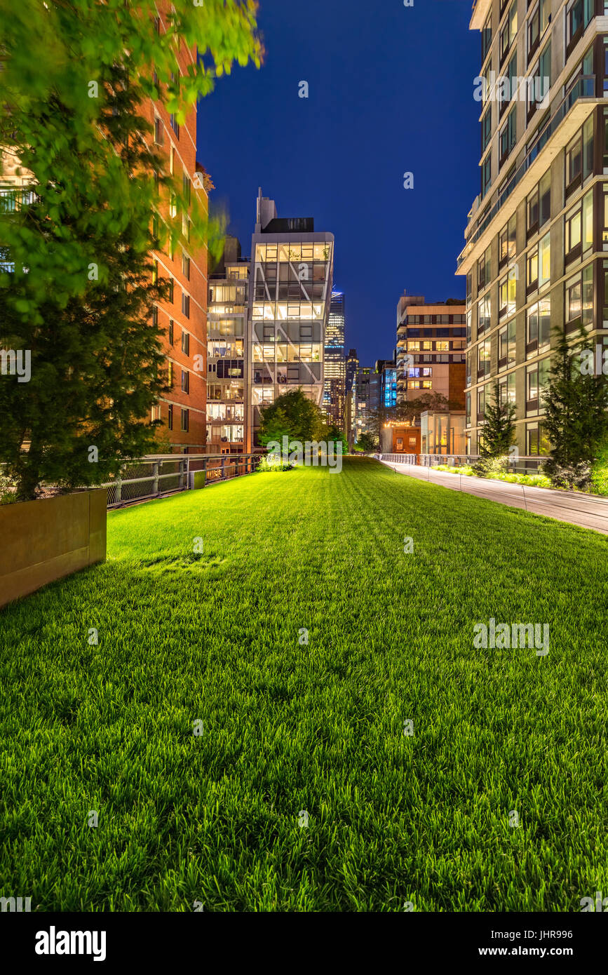 Highline promenade at twilight with illuminated high-rises in Chelsea. Manhattan, New York City - Stock Image