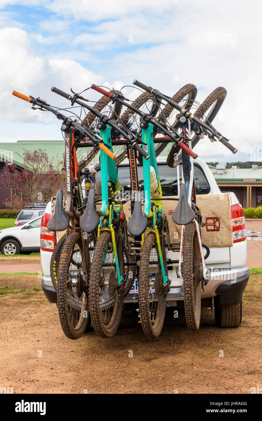 Muddy mountain bikes on a bike rack on the back ute in Western Australia - Stock Image