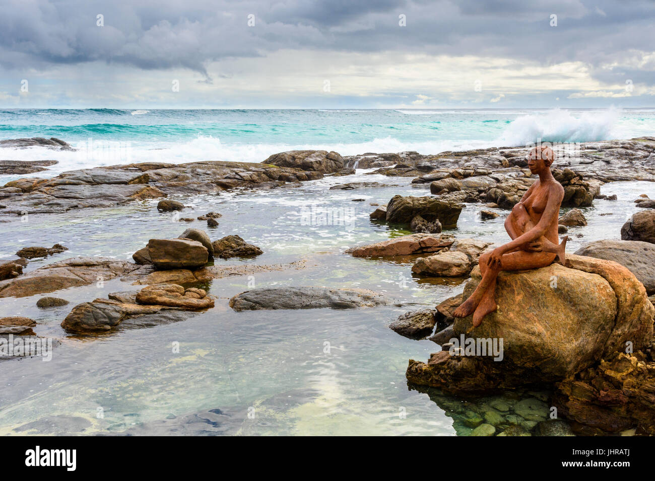 The rock pools near Margaret River river mouth with Russell Sheridan's Layla public art sculpture on a rock, Prevelly, - Stock Image
