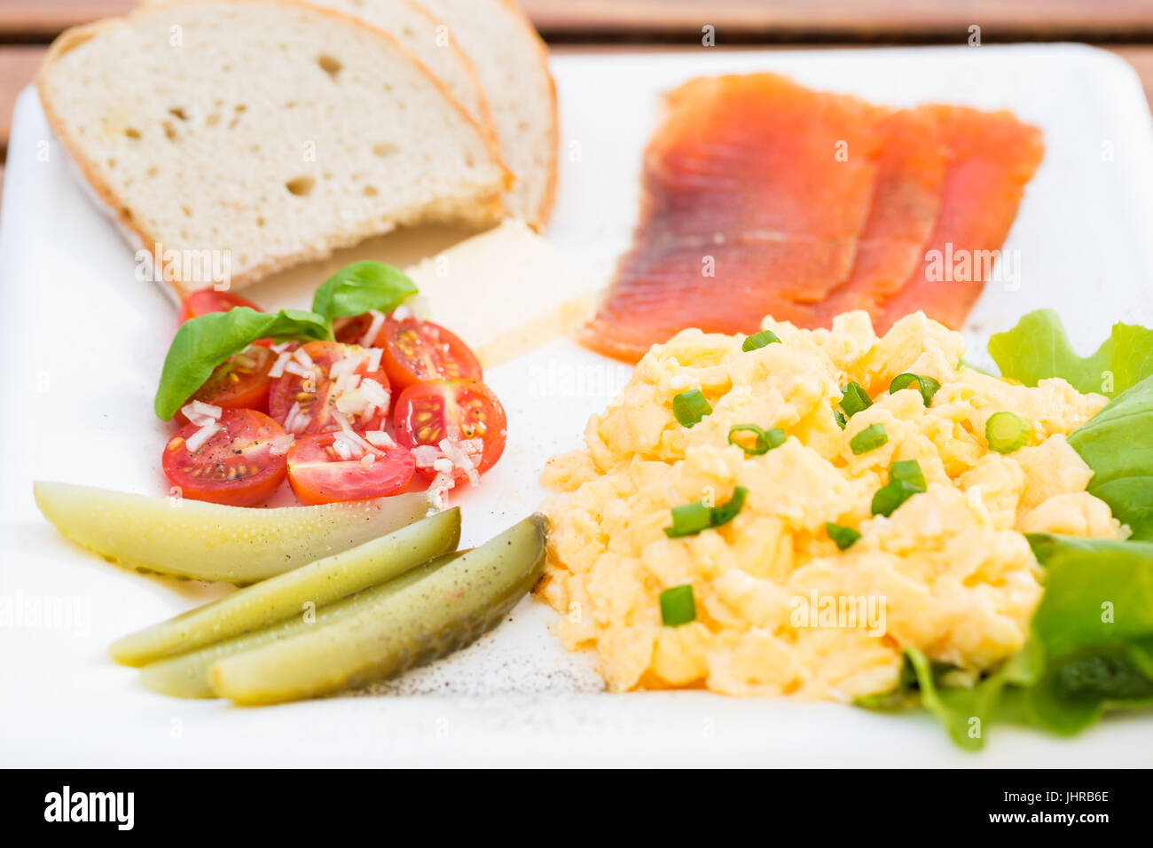 Breakfast set, scrambled eggs with chives, fish, cucumber, tomato and bread - Stock Image