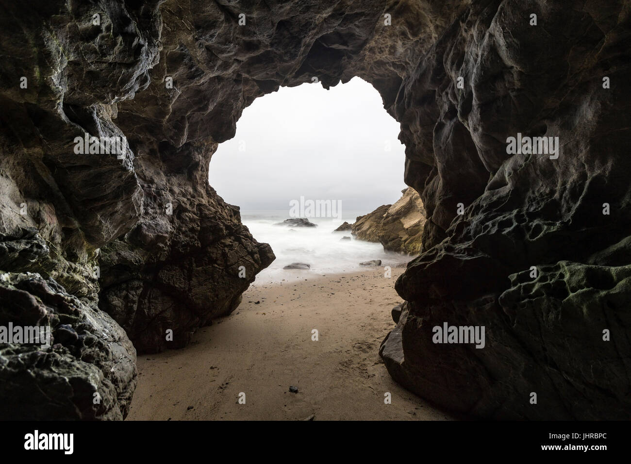 Sandy floor sea cave with motion blur water at Leo Carrillo State Beach in Malibu, California. - Stock Image