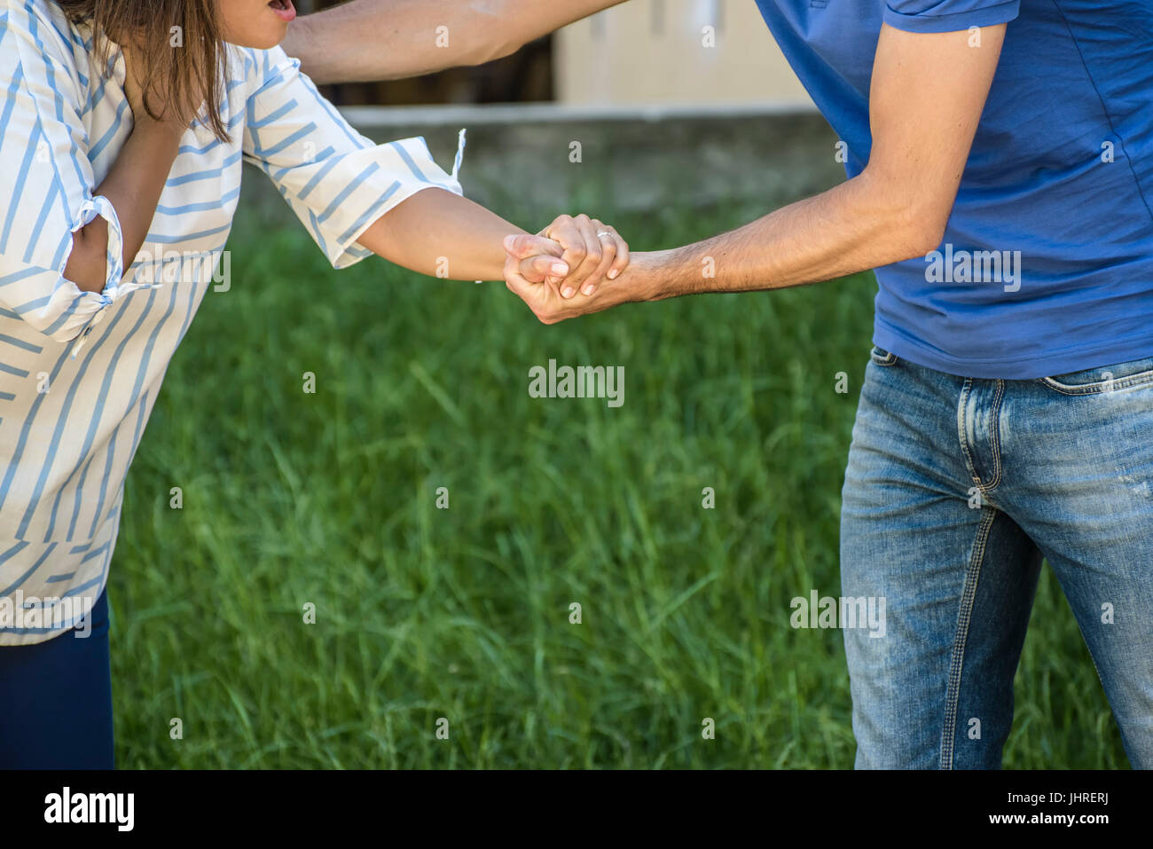 guy making the heimlich maneuver to a girl while she's choking Stock Photo