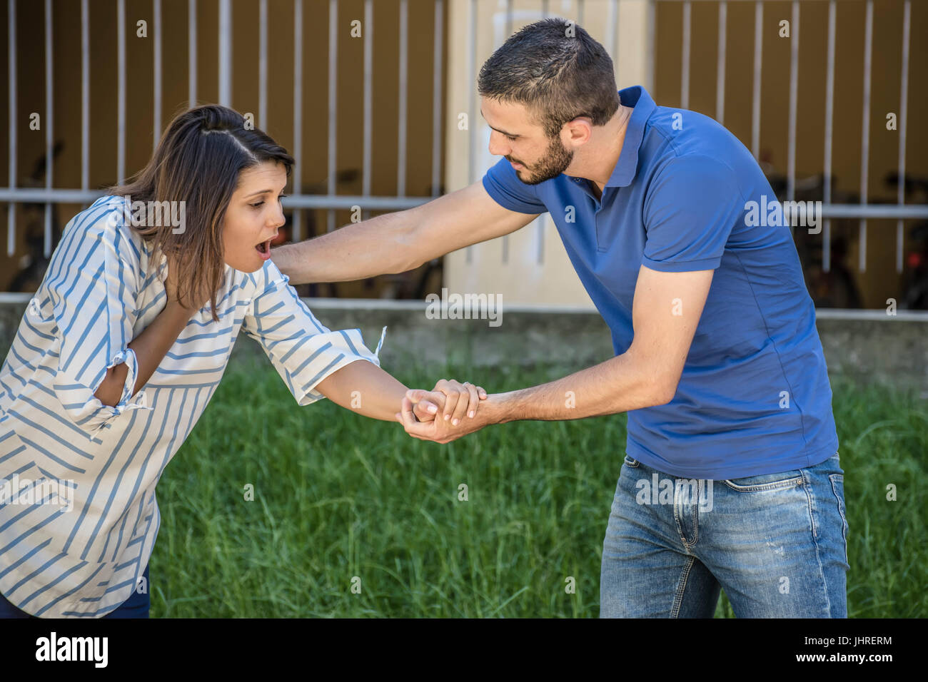 guy making the heimlich maneuver to a girl while she's choking - Stock Image