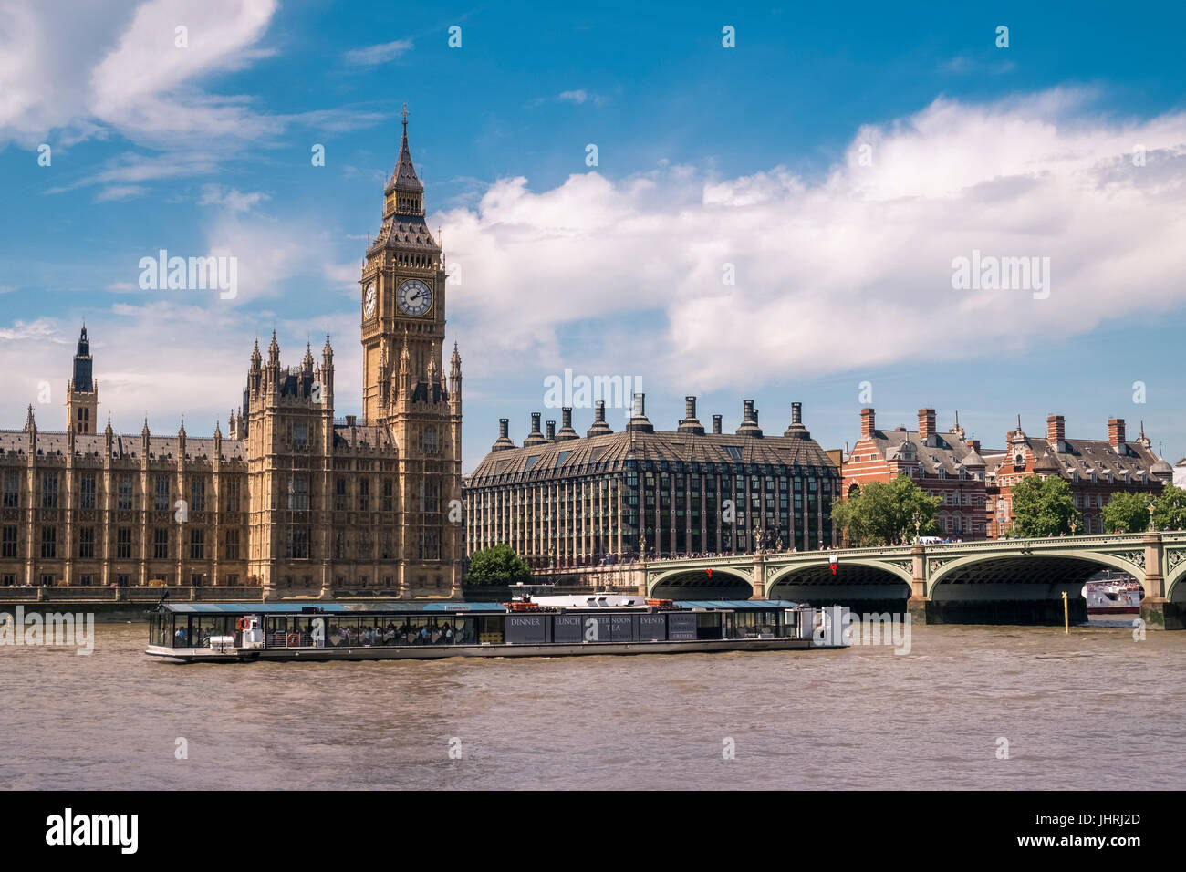 Tourists aboard a floating river restaurant on the river Thames outside the Houses of Parliament, Westminster, London, - Stock Image