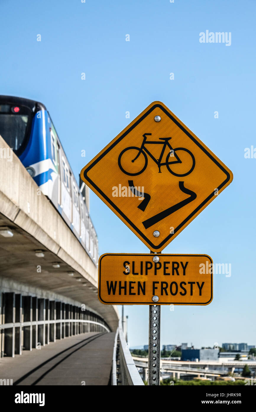 A Slippery When Frosty sign and a skytrain on North Arm Canada Line skytrain bridge over the Fraser river between - Stock Image