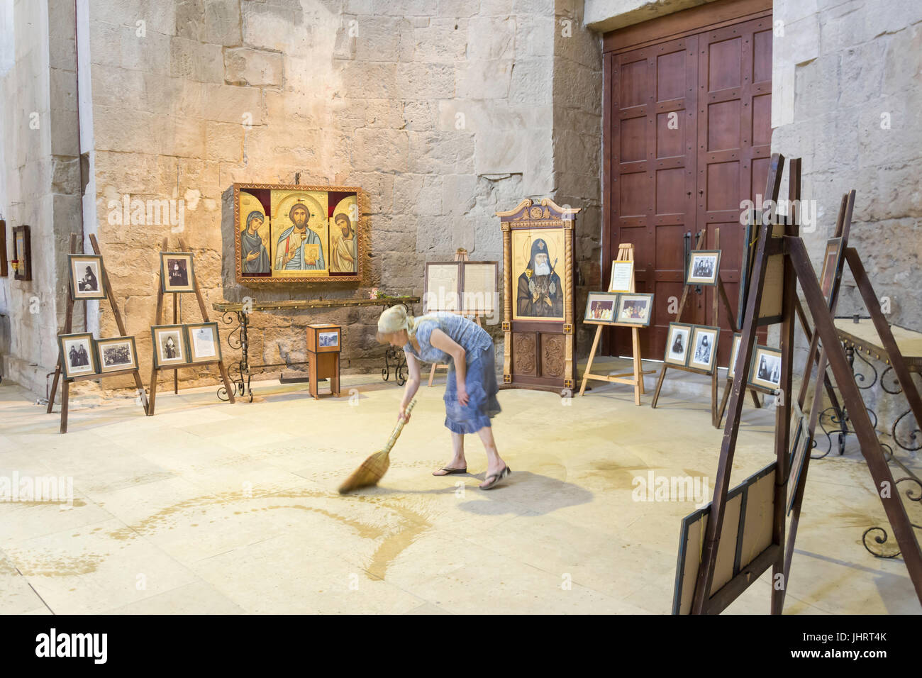 Woman sweeping floor of Cathedral of the Nativity of the Virgin, Gelati Monastery, Kutaisi, Imereti Province (Mkhare), - Stock Image