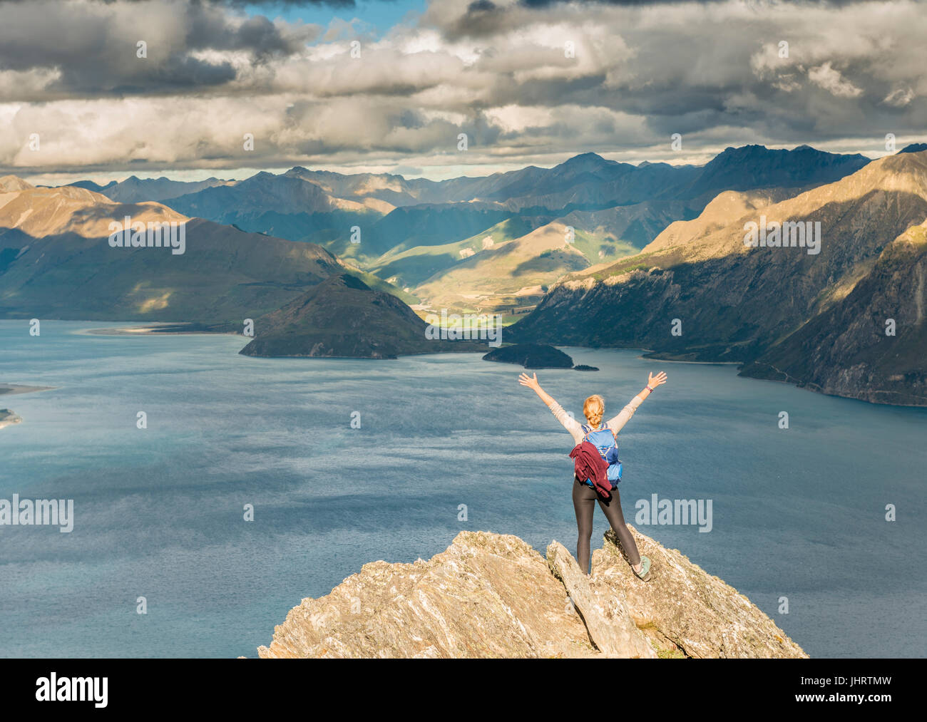 Female hiker on a rock, stretching arms in the air, Lake Hawea and mountain landscape, Isthmus Peak, Otago, South - Stock Image