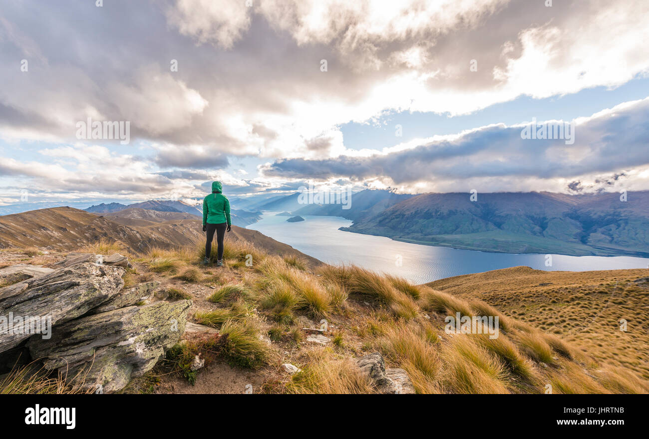 Female hiker woman looking at lake, Lake Hawea and mountain landscape, Isthmus Peak, Otago, South Island, New Zealand Stock Photo