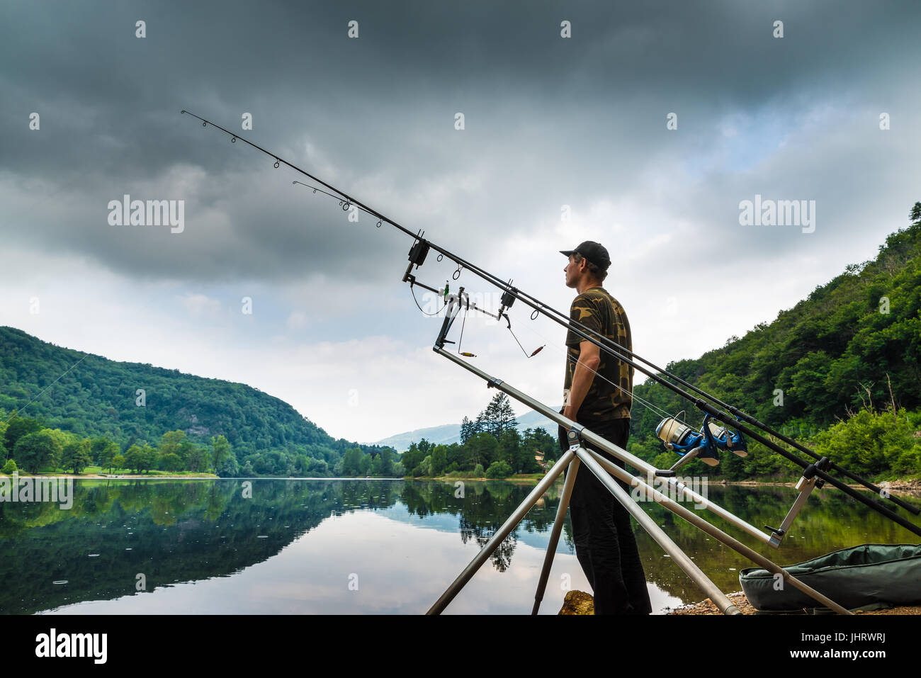 Fishing adventures, carp fishing. Angler on the shore of a lake in a morning with dark sky and grey clouds - Stock Image