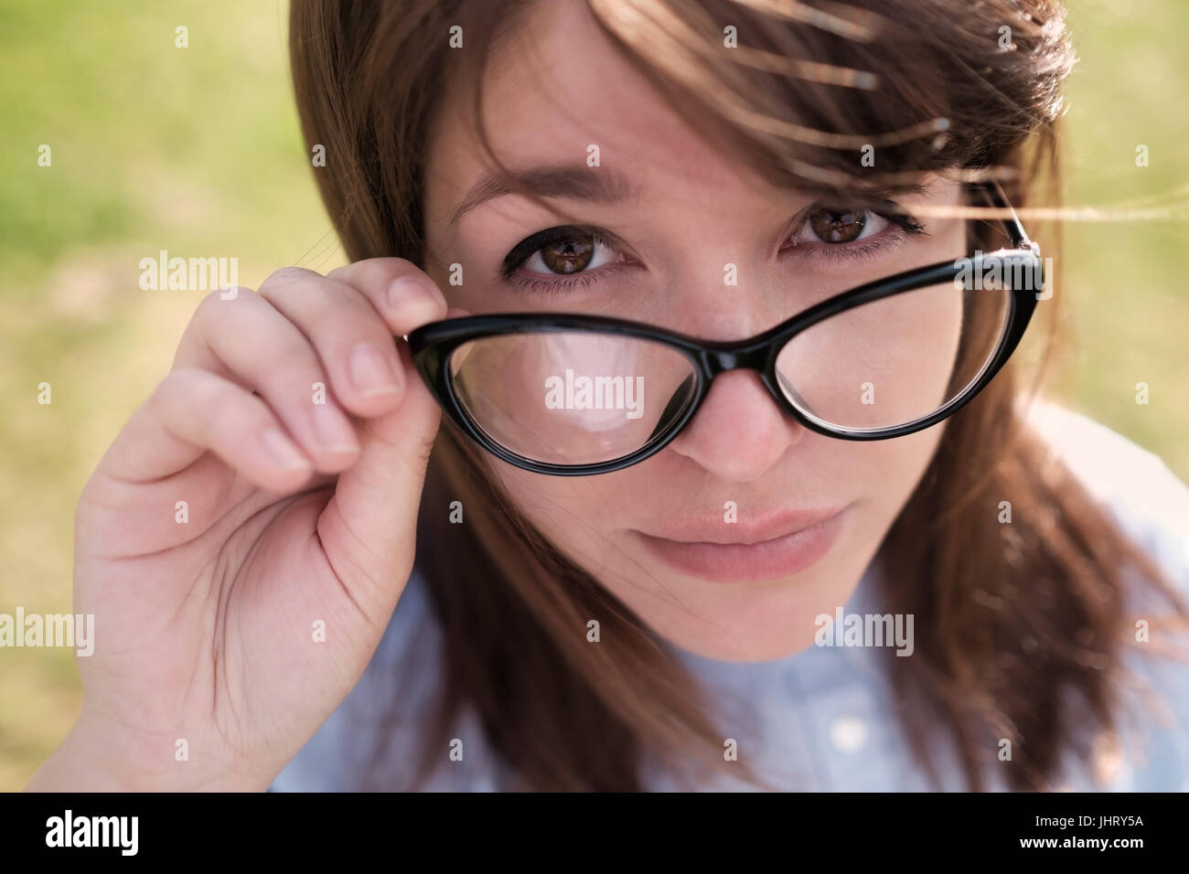 33a8630d3c6 Beautiful young woman adjusting her glasses and smiling at you over blured  green nature background.